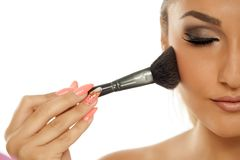 Woman applying blush. Young beautiful woman applying blush with a brush on a white background Stock Image