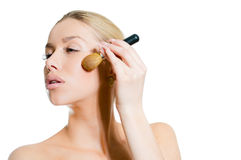 Young beautiful woman applying blush Stock Photography