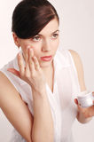 Young beautiful woman applying cream Stock Images