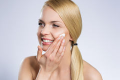 Young beautiful woman applying cream on face looking away Royalty Free Stock Photo