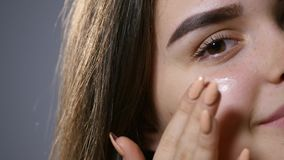 Young beautiful woman applying cream on her face, isolated on gray stock footage