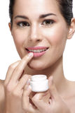 Young beautiful woman applying cream treatment on skin Stock Photography