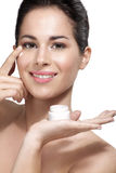 Young beautiful woman applying cream treatment on skin Stock Photo