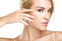 Young beautiful woman applying creme on her skin Royalty Free Stock Photo