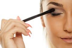 Woman applying eye-shadow Stock Photo