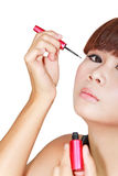 Young beautiful woman applying eyeliner Royalty Free Stock Photography