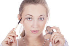 Young beautiful woman applying eyeshadow on eyes Royalty Free Stock Photos