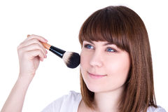 Young beautiful woman applying make up with brush isolated on wh Stock Image