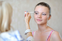 Young beautiful woman applying make-up by professional make-up a Royalty Free Stock Images