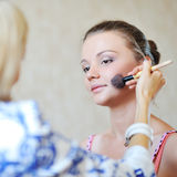 Young beautiful woman applying make-up by professional make-up a Stock Image