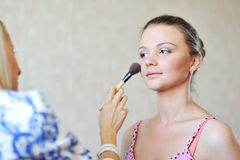 Young beautiful woman applying make-up by professional make-up a Royalty Free Stock Photo