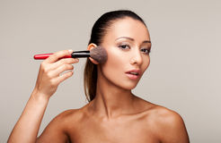 Young beautiful woman applying makeup Stock Photos