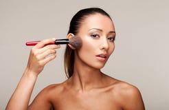 Young beautiful woman applying makeup Stock Photos