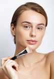 Young beautiful woman applying makeup on face Stock Image