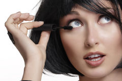 Young beautiful woman applying mascara makeup on eyes by brush Stock Photography