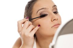Woman applying mascara. Young beautiful woman applying mascara to her eyelashes in front of a mirror Stock Images
