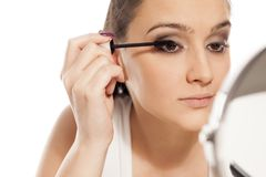 Woman applying mascara. Young beautiful woman applying mascara to her eyelashes in front of a mirror Stock Photos