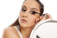 Woman applying mascara. Young beautiful woman applying mascara to her eyelashes in front of a mirror Royalty Free Stock Photography