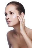 Young beautiful woman applying moisturize cream Royalty Free Stock Photography