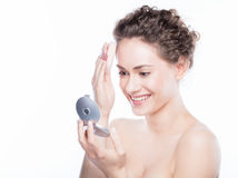 Young beautiful woman applying powder on her skin Stock Photo