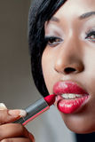 Young beautiful woman applying red lipstick stock photo