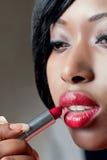 Young beautiful woman applying red lipstick Stock Photo