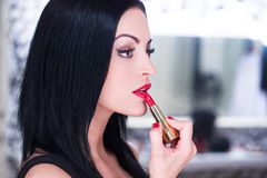Young beautiful woman applying red lipstick Royalty Free Stock Images