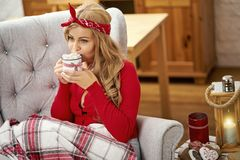 Young beautiful woman in armchair with a cup of hot chocolate and a blanket during Christmas time stock images