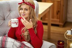 Young beautiful woman in armchair with a cup of hot chocolate and a blanket during Christmas time royalty free stock image