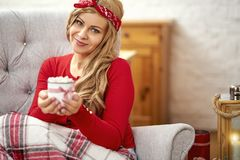 Young beautiful woman in armchair with a cup of hot chocolate and a blanket during Christmas time stock photo