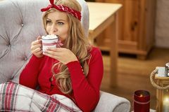 Young beautiful woman in armchair with a cup of hot chocolate and a blanket during Christmas time stock photos