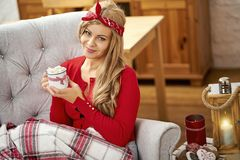 Young beautiful woman in armchair with a cup of hot chocolate and a blanket during Christmas time royalty free stock photo