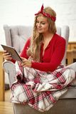Young beautiful woman in an armchair with a tablet wrapped in a blanket during Christmas time stock images