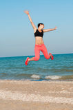 Young beautiful woman athlete jumping on the beach Stock Photos