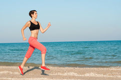 Young beautiful woman athlete running on the beach Stock Photo