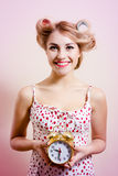 young beautiful woman attractive funny blond pinup girl holding alarm clock and charming smiling looking at camera Royalty Free Stock Images