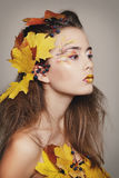 Young beautiful woman with autumn make up and leaves on head. Be. Young beautiful woman with autumn make up and leaves on head stock image