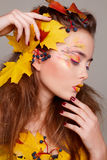 Young beautiful woman with autumn make up and leaves on head. Be. Young beautiful woman with autumn make up and leaves on head stock photography