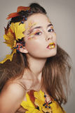 Young beautiful woman with autumn make up and leaves on head. Be. Young beautiful woman with autumn make up and leaves on head royalty free stock images