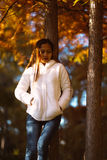 Young beautiful woman in autumn park on sunny day, Young woman in white coat during sunset in the park Royalty Free Stock Photos