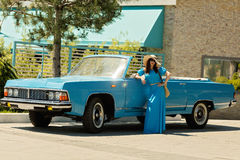Young beautiful woman in azure long dress near a retro car. Stock Images
