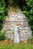Young beautiful woman on a background of a stone old wall entwined with ivy. Stock Photos