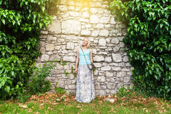 Young beautiful woman on a background of a stone old wall entwined with ivy. Royalty Free Stock Image