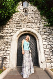Young beautiful woman on a background of a stone old wall with a small vintage door entwined with ivy. Royalty Free Stock Images