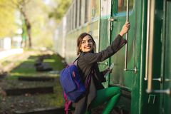 Young beautiful woman with backpack go to travel by train at the train station. Travel and lifestyle concept royalty free stock photos