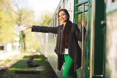 Young beautiful woman with backpack go to travel by train at the train station. Travel and lifestyle concept stock photography