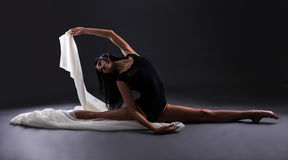 Young beautiful woman ballerina in black body suit sitting in tw Royalty Free Stock Photography
