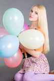 Young beautiful woman with balloons sitting over grey Royalty Free Stock Photos