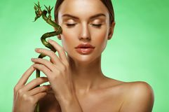 Young beautiful woman with bamboo over green background. Close up Royalty Free Stock Image