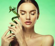 Young beautiful woman with bamboo over green background. Close up Royalty Free Stock Photos